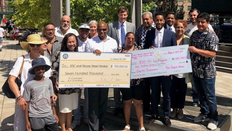 Brooklyn Borough President Eric L. Adams, NYCEDC President and CEO James Patchett, Council Member Antonio Reynoso, and community members celebrate a $2.7M investment to renovate Moore Street Market