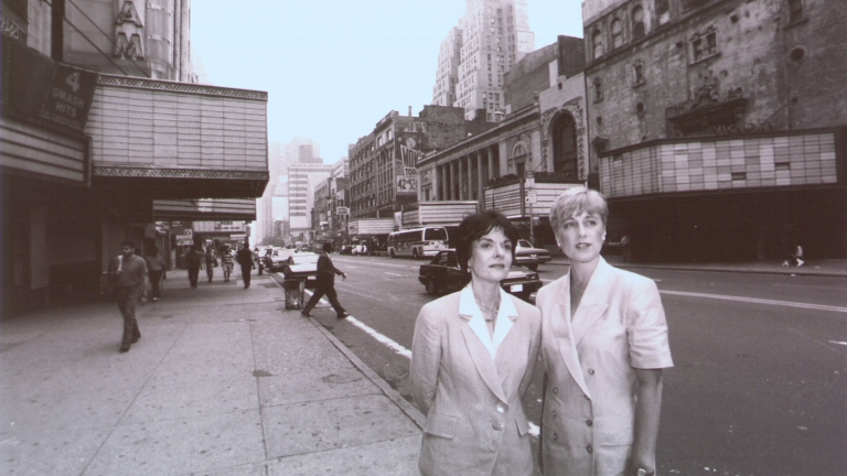 Rebecca Robertson (right) and Cora Cahan (left) stand with the empty theatres and stores of 42nd Street in the background. Credit: New York Times