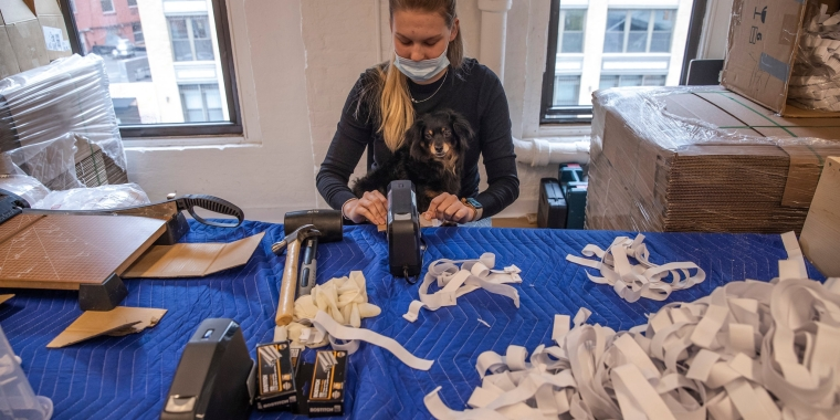 Vladislava Bulatnikova stapling elastic to face shields on an assembly line at Consortium, a company that has converted a loft in the meatpacking district into a factory for personal protective equipment.Credit...Brittainy Newman/The New York Times