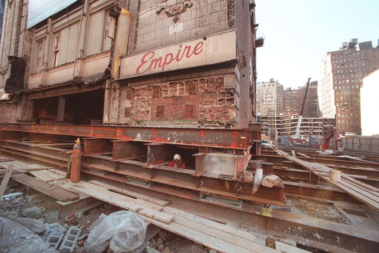 Construction workers putting the Empire Theatre on lifts for its move west. Image: The New York Times.