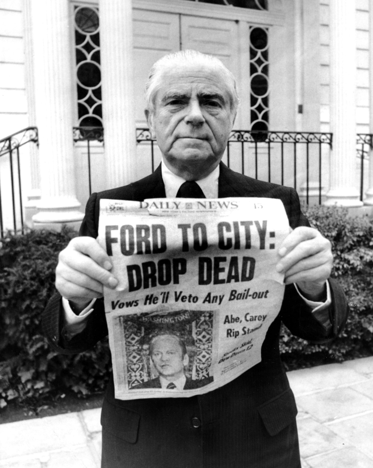"""Ford to City: Drop Dead"" was the famous headline that ran on October 30th, 1975 in the New York Daily News, as shown here held by Abraham Beame, Mayor of New York City from 1974-1977. Image: Getty Images."